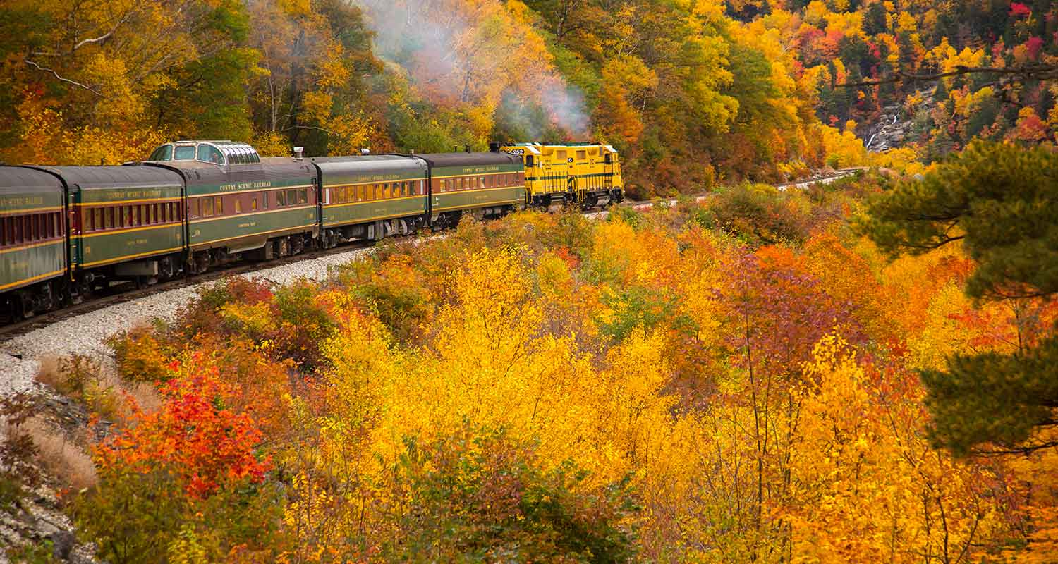 Crawford Notch, New Hampshire - 10/14/2015: The Conway Scenic Railway train just west of Bartlett. Hardwood trees are showing peak fall color in the White Mountain National Forest.